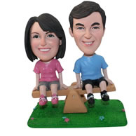 Custom couple sitting on a teetertotter figurines