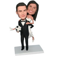 Groom in black suit handing with a soccer ball carrying bride in white wedding dress bobblehead