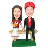 Boyfriend in black suit and girlfriend in red shirt handing with a bunch of flowers bobblehead