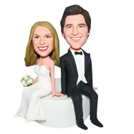 Groom in black suit and bride in white wedding dress handing a bunch of flowers bobblehead