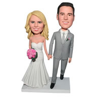 Groom in grey suit and bride in white wedding dress handing with a bunch of flowers bobblehead