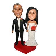 Groom in black suit and bride in white wedding dress handing a bunch of flowers custom bobblehead