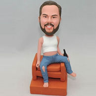 Personalized bobbleheads sit in the chair with a bottle of beer