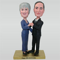 Huaband in black suit and wife in blue dress with their 50th anniversary custom bobbleheads