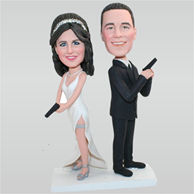 Funny groom in black suit and bride in white wedding dress holding a gun custom bobbleheads