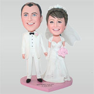 Groom in white suit and bride in white wedding dress holding a bunch of flowers custom bobbleheads